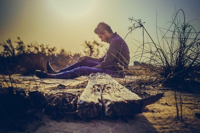 Smutný muž sedí na zemi