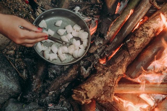Žena pripravuje rybu nakrájanú na kúsky na suchej panvici nad ohňom