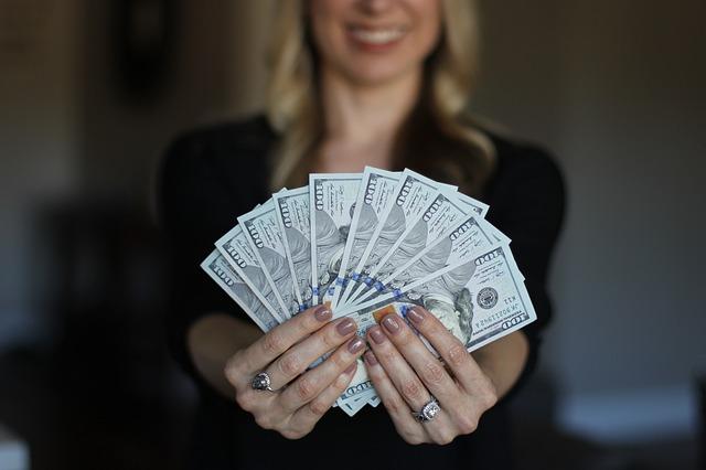 Žena drží v rukách papierové bankovky.jpg