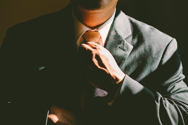 Muž v obleku sa drží za kravatu.jpg