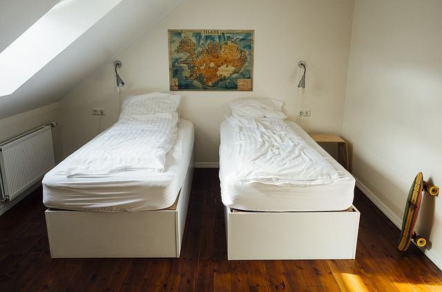 Spálňa v podkroví s dvoma posteľami, na ktorých sú hrubé matrace.jpg