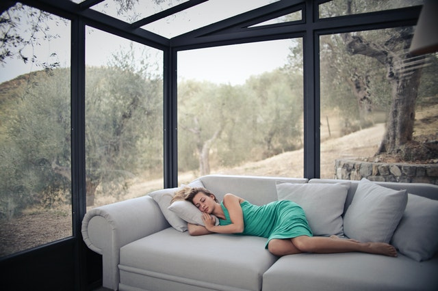 Žena v zelených šatách spí na gauči v miestnosti so sklenenými stenami