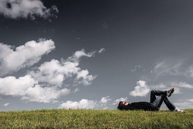 Chlap leží s prekríženými nohami na lúke