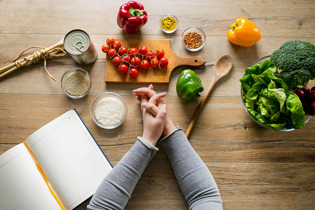 woman-leaning-on-table-with-various-ingredients-and-a-diet-planning-book